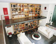 La mezzanine de ce loft coupe une bibliothèque en deux. Le garde corps n'est constitué que d'une barre en métal, ce qui ouvre au maximum la vue.