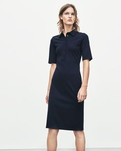 An ultimately minimalist shirt dress with a fitted silhouette. Firm cotton jersey with a neat, 90's look . Above knee length, t-shirt sleeve and small collar.