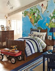 A wall-sized decal of a detailed map inspires curiosity about geography every day in this room. We created a system with flags to mark all the places that have been visited, and included a bolster pillow on top of the bed that's made to inspire further exploration. A child's fascination with insects is celebrated in framed art, wall sculptures and the sheeting.
