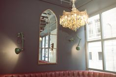 Reclaimed 1880's church window restored and made into a mirror framed by industrial wall mounted angle-poise lamps.  Decorative chandelier with careful chosen coloured teardrops. Framed perfectly by the Farrow and Ball Railings painted wall.  agapanthusinteriors.com