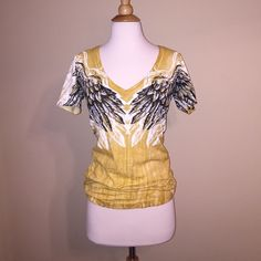 ❗️SOLD ❗️Gold Rhinestoned Angel Wing Shirt Fits very small! Could fit an extra small or a small and would be really tight fighted on a medium. Wing design on front and back. Rhinestoned word on the back. Low V neckline. Sinful Tops Tees - Short Sleeve