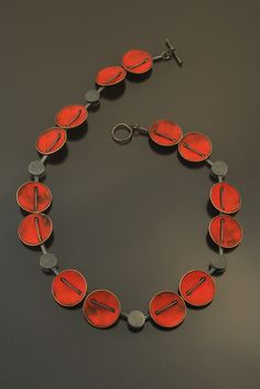 Love that the cable or cord goes through the beads! Necklace | Angela Gerhard. 'Red Coupling'. Torch-fired enamel on copper, sterling. Matte finish