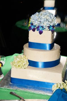 Wedding cake- three tier cake with white icing and blue ribbon on the bottom of each tier -the top and bottom tiers are square while the middle tier is a circle -the top tier has blue hydrangeas ans dark blue orchids on it