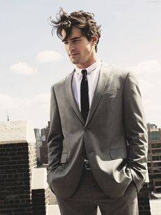 He's tall, dressed in a fine gray suit, white shirt, and black tie with unruly dark cooper-colored hair and intense, bright gray eyes. #christiangrey