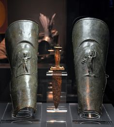 Dagger and pair of bronze gladiator's greaves (leg guards) from Pompeii decorated with relief of Jupiter (left) and Neptune (right), Gladiators – Death and Triumph at the Colosseum exhibition, Museum und Park Kalkriese