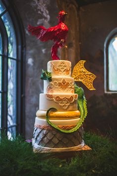 "The cake had four layers with a bottom layer of dragon scales and the top two reflecting the embroidery in the bride's dress. The middle layer was The One Ring, with the couple's motto on it ""A Light in the Darkness."" A 3D dragon wrapped around the layers and a 3D phoenix took flight off the top. The couple cut it using a sword which also had our motto engraved upon it."