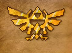 This Perler bead sprite is a depiction of the Hyrule Crest from The Legend of Zelda series. (Original Perler design is, as far as I can tell, by the