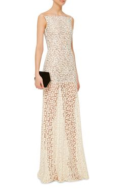 Rendered in embroidered floral lace, this **Huishan Zhang** sleeveless gown features an apron neckline, a fitted mini length silhouette, and a sheer floor length skirt rendered in floral embroidery.