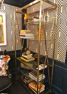 LOVE the brass bookshelf with the wallpaper