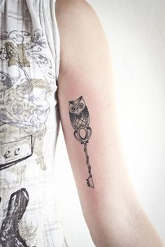 small owl with a key - tattoo