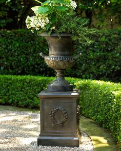 Neiman Marcus Classic Urn Planter & Laurel Wreath Pedestal. Classically styled urn planter and sturdy pedestal base with laurel wreath decoration are made of molded resin with a hand-painted antiqued black finish. Both pieces are outdoor safe; for best results, spray with a polyurethane coating annually. $235.00-250.00.