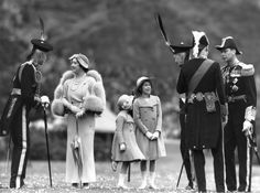 Queen Elizabeth talking to Lord Elphinstone during an inspection of the Royal Company of Archers at the Palace of Holyroodhouse, Edinburgh. Her husband King George VI is on the right; Princesses Elizabeth and Margaret Rose are in the centre. (Photo by Fox Photos/Getty Images). 1937