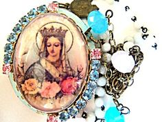 """$125 Size: 20"""" long plus 2"""" Locket  Color: Light Blue Enamel, Pink & Blue Rhinestones, Brass, Copper   Type: Enamel Cameo Locket Bead Necklace  Vintage & Artisan    White glass beads with 8mm faceted pink & blue opaque glass beads on antique brass chain.  The front of the v=intage locket is pale blue enamel with light blue and pink rhinestones. The back of the locket is toned antique copper. The drop holding the locket depicts the Miraculous Medal - Our Lady of Grace.  The glass cabochon…"""