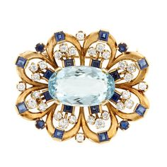 Gold, Aquamarine, Diamond and Sapphire Brooch  One oval aquamarine ap. 11.00 cts., 28 round diamonds ap. 1.45 cts., 16 square-cut & 4 round sapphires ap. 2.40 cts., c. 1945