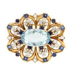 Gold, Aquamarine, Diamond and Sapphire Brooch  One oval aquamarine ap. 11.00 cts., 28 round diamonds ap. 1.45 cts., 16 square-cut & 4 round sapphires ap. 2.40 cts., c. 1945