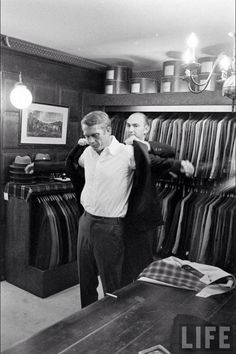 """The """"King of Cool"""" Steve McQueen being fitted at the tailors, note the Harrington draped across the cutting table."""