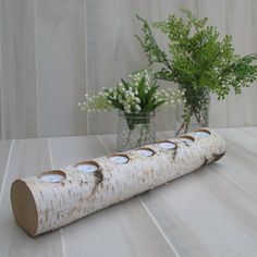 porte-bougies DIY en tronc de bouleau et bouquets de muguets et plantes vertes sur la table