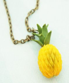 This necklace features a handmade pineapple pendant made from polymer clay. The pendant measures 3 cm tall and is attached to a bronze chain necklace that measures 24 inches in length. SKU 1432