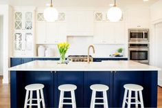 Navy Blue and White Kitchen Featuring Large Cabinets and Kitchen Island with Stools
