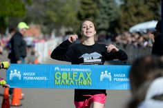 Description of . Alysha De-Laurell crosses the finish line in the women's division of the Colfax Marathon with a time of 2:58:40 of the 9th annual Colfax Marathon May 18, 2014. The 26.2 mile Marathon runs through Denver's iconic landmark Mile High Stadium (twice), Sloan's Lake, City Park, Colfax Avenue through Lakewood and Aurora. The Marathon started and finished in City Park where runners enjoyed the rest of the day listening to music by Chris Daniels and the Kings. (Photo by John ...