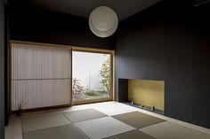壁の黒の中に、伊東豊雄作のペンダント照明の白、窓越しに見える植栽の緑や花それぞれが際立つ、独創的でモダンな和室。