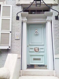 Nickel hardware so beautiful on soft blue door. Interesting arched piece holding lantern above the door