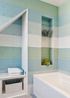 Contemporary bathroom features sloped nook filled with built-in bench accented with white, green and blue glass subway tiles which continues to the bathtub shower combo lined with tiled niche filled with glass shelves.