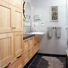 "These homeowners opened up their space by getting rid of two small closets and adding task and ambient lighting to help create the illusion of a larger room. Little width remained after incorporating the tub and toilet, so a shallow cabinet was incorporated. Our favorite detail? The playful ""dry riverbed"" of stones in the floor."