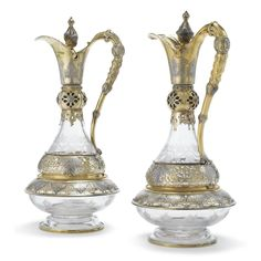 A pair of Victorian parcel-gilt mounted etched glass presentation claret jugs, John S. Hunt, London, 1861 baluster bodies etched with ivy, the pierced collars chased with gothic foliage, matching knops, both covers engraved with two crest
