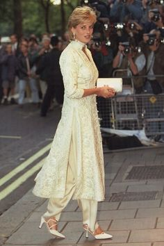 JULY 1996 - A month before Charles and Diana's divorce was announced, she was pictured wearing an off-white shalwar kameez to a cancer fundraiser in London. The pantsuit was a gift from friend Jemima Khan.