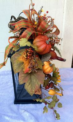 This is a fall floral lantern swag with burlap and printed ribbons, sunflowers, pumpkins, gourds, berries and a grapevine pumpkin. This swag