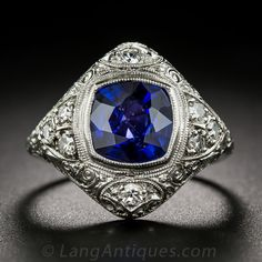 3.00 Carat Sapphire, Platinum and Diamond Edwardian Ring. A rich royal blue cushion-cut sapphire, weighing 3.00 carats, radiates from within a finely millegrained bezel-setting, in the center of a billowy lozenge shape platinum mounting, glittering on all sides with small white single-cut diamonds. The intricately detailed ring dates back to the first or second decade of the last century and artfully melds Edwardian-era femininity with the geometric symmetry of the emerging Art Deco period