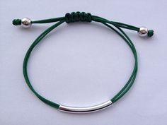 A simple, yet very elegant bracelet available in many different colors.  Cord colors: black, blue, camel/brown. green, red, yellow, pink, baby blue, white, gray, beige  The tube is either silver plated or gold plated.  The size of the bracelet is adjustable so that it fits almost everyone.  No returns accepted.