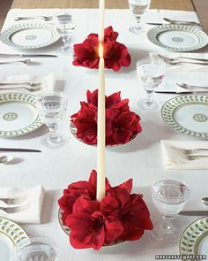 Blooming Centerpieces  With the help of these candle and flower centerpieces, the whole table will shine. For each one, use candle wax to attach a small floral frog to the center of a shallow bowl. Push a taper into the floral frog to secure. Pour water into the bowl. Clip amaryllis blooms (or other large flowers) from their stems, and arrange them in the bowl around the candle.