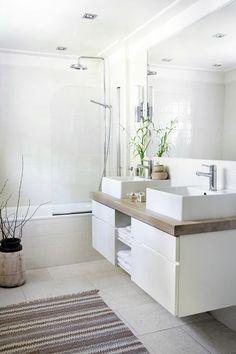 Un tapis bohème et quelques plantes réveillent une salle de bains blanche