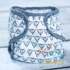 A diaper cover with Harry Potter inspired Deathly Hallows symbol print. Position of design may not be as pictured.   Features: * Choose from a slim style fit that is OSFM (one size fits most) on babies from 7lbs to 35lbs + or a regular OSFM cover that fits 10-40lbs +  *Snap down rise  *P...