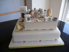 """80th birthday cake for my mum who loves to bake.  I wanted to include her grandaughter and great grandaughters in the scene.  Two """"helping"""" with the baking, the eldest wanted to be dancing but as the cake had to travel over 250 miles I made her doing the splits instead for stability.  Latest addition to the family also included.  Kitchen units and fridge freezer made from rice krispies. Marbled worktop looked very authentic. Coloured piping gel added to the kitchen sink when we reached the…"""