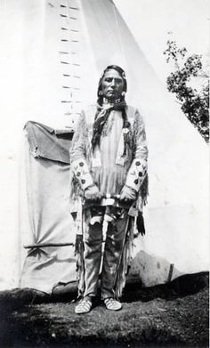 """circa 1930 Theodore """"Ted"""" Last Star wearing traditional beaded dress, gauntlets, and moccasins. Tipi in background .:"""