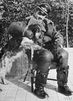 """meninroad: """"© IWM (HU 4128) Major Adolf Galland, the leading ace of the Luftwaffe during the Battle of Britain, seated in a chair with his dog. """""""