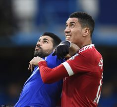 Chelsea striker Costa (left) and Manchester United defender Chris Smalling keep their eyes on the ball as they tussle to win it