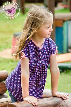 This tunic features a front yoke with pintuks and a wide comfortable bodice. It closes at the front yoke with 3 buttons or snap fasteners