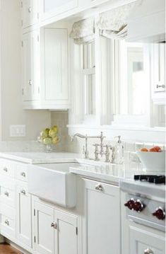 Beautiful light filled kitchen with white cabinets, white quartz countertops and polished nickel hardware. The white counters pair with gray beveled subway tile. A large farmhouse sink pairs with a polished chrome bridge faucet that sits below a wide window. by lelia