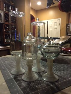 Dollar store jars, bowls, and vases glued to spray painted dollar store candlesticks.