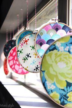Colorful fabric in embroidery hoops makes a bold statement as a window display. A simple, colorful way to decorate for spring and summer.