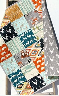 Baby crib quilt with deer heads, fawn bear and Aztec fabrics with a neutral deer background fabric for a baby boy or girl nursery room theme.