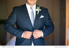 Groom getting dressed in a navy suit and silver tie | Photographer: Adene Photography