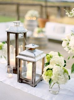 "Half of the tables will have centerpiece trios consisting of a 12"" cylinder vase with submerged white dendrobium orchids, a vintage white lantern, and a square vase overflowing with cream hydrangeas, dusty miller, and succulents."