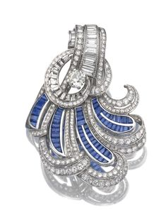 SAPPHIRE AND DIAMOND BROOCH.    Of stylised feather design, set with calibré-cut sapphires, single-, circular-cut and baguette diamonds.