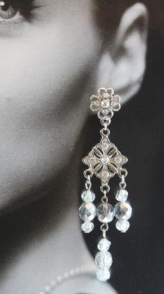 Brincos estilo chandelier, em metal prateado, com aplicação de strass de cristais Swarovski. No pendant, cristais tchecos metalizados em tons de branco/prata.  Comprimento total: 8 cm R$32,00