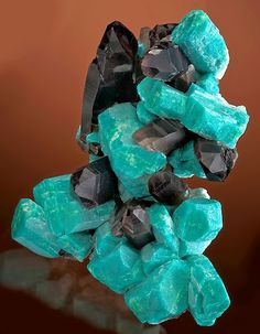 Amazonite crystals with dark Smoky Quartz. Amazonite is a translucent to opaque feldspar gemstone with a pretty green color. It is the greenish variety of the mineral Microcline. Amazonite is named after the Amazon River of South America. There are no Amazonite deposits that exist in the Amazon region, so presumably this stone is named to its resemblance in color to the green of the tropical rainforest.